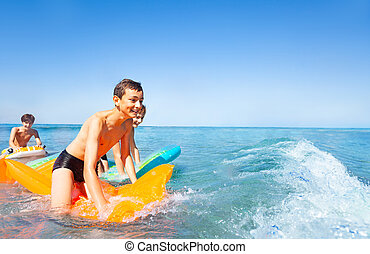 Happy boys riding the waves on air mattresses