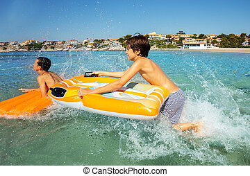 Happy boys riding the waves with air mattresses