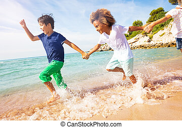 Happy boys running in shallow water on the beach