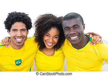 Happy brazilian football fans in yellow sitting on couch on...