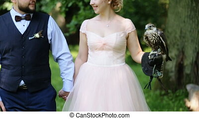 Happy bridal couple walking through the forest holding hands with beautiful falcon sitting on bride's glove