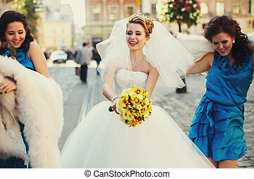 Happy bride and bridesmaids dance on the old street