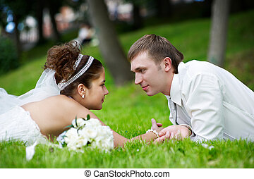 Happy bride and groom are on grass