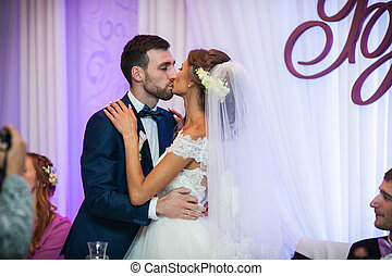 Happy bride and groom at wedding reception table posing and kissing closeup
