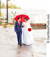 Happy Bride and groom at wedding walk with red umbrella. Autumn style concept.