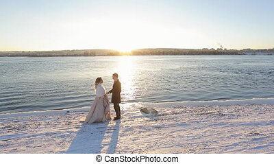 Happy bride and groom bathe in rays of setting sun on coast of river in winter.