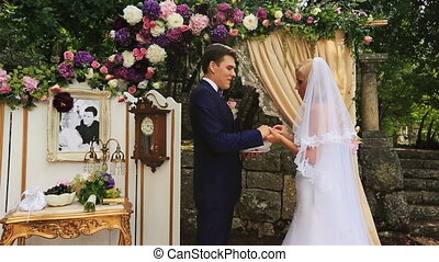 Happy bride and groom exchaning rings in the wedding tent in Montenegro, Budva