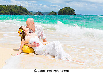 Happy bride and groom having fun on a tropical beach. ...