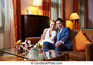 Happy bride and groom in interior of hotel room