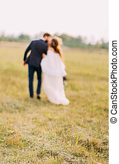 Happy bride and groom kissing on the field at countryside