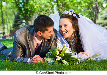 Happy bride and groom lying on grass