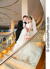 Happy bride and groom on ladder at hotel