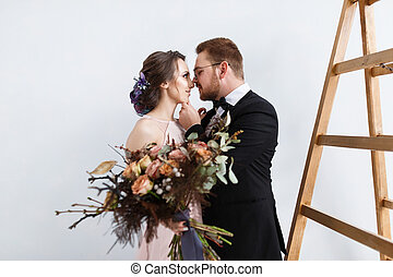 Happy bride and groom on ladder at studio