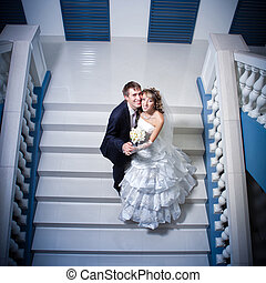 Happy bride and groom on ladder at wedding walk