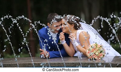 happy bride and groom standing near the fountain in the park