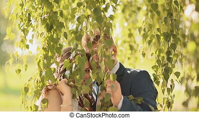 Happy bride and groom together hiding under the branches of a birch.
