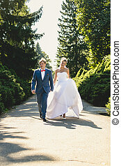 bride and groom walking at summer park at sunny day