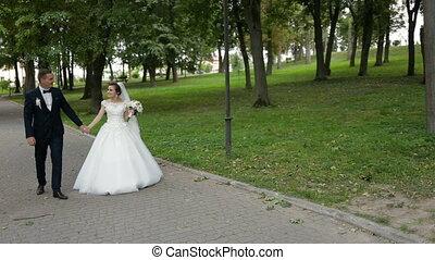 Happy bride and groom walking in park.