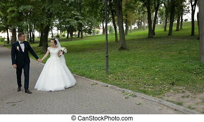 Happy bride and groom walking in park.