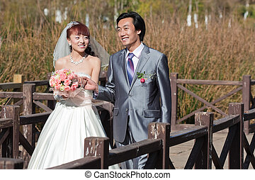 happy bride and groom walking over bridge (2)