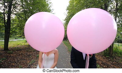 Happy bride and groom with balloon