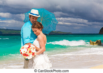 happy bride and groom with blue umbrella and wedding bouquets on the tropical coast
