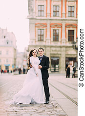 Happy bride and stylish groom running hugging on the background old sunny city