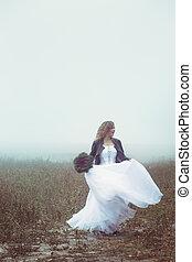 Happy bride dancing in the field