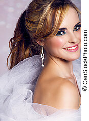 happy beautiful bride with long blond hair in ponytail waring artistic smoky eyeshadow and smiling on bokeh background.