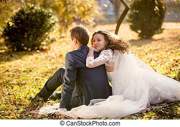 happy bride hugging groom sitting on yellow leaves at park