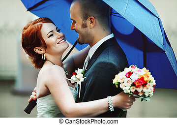 Happy bride hugs a groom under blye umbrella