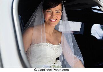 Happy Bride in Limo - Attractive bride sitting in car and...
