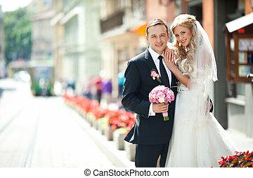 Happy bride leans on groom's shoulder standing between flowerpots on the street