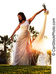 Happy bride over sunset