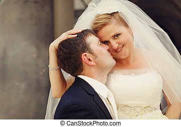 Happy bride smiles while groom touches her cheek