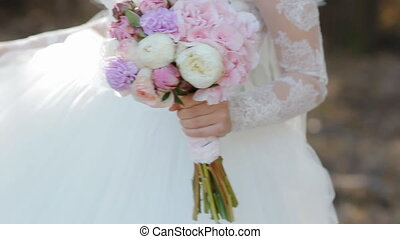 Happy bride spinning around outdoor posing to photographer and holding beautiful bouquet of flowers