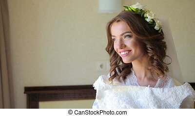 Happy bride tries on wedding dress and smiling