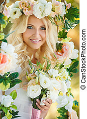 Happy bride with a bouquet of flowers in the park.