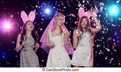 Happy bride with girlfriends dancing drinking champagne at bachelorette party