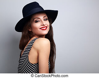 Happy bright makeup woman in fashion black hat and red lips posing with happy smiling on blue background