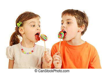 Happy brother and sister lick colorful lollipops isolated on...