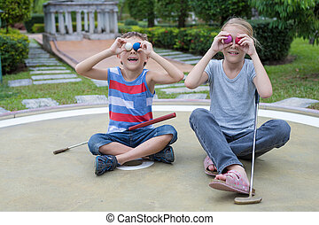 Happy brother and sister playing mini golf in a park at the day time. People having fun otdoors. Concept of good leisure.
