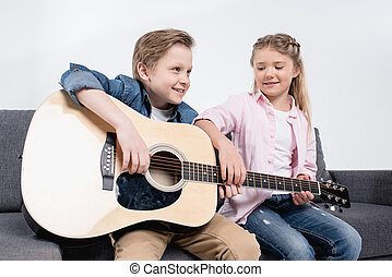 happy brother and sister playing on guitar together while sitting on sofa