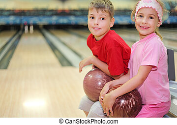 Happy brother and sister sit and hold balls in bowling club;...