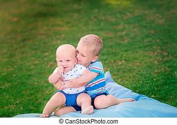Happy brothers playing on the grass