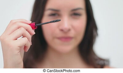 Happy brunette applying mascara on her eyelashes against a...