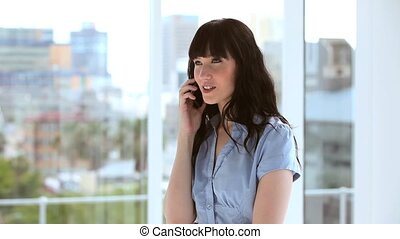Happy brunette businesswoman using her cellphone