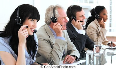 Happy brunette call centre agent working with her colleagues