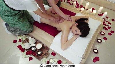 Happy Brunette Enjoying a Massage in Four Hands
