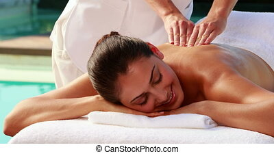 Happy brunette enjoying a massage p